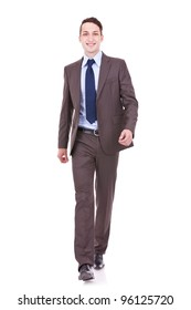 young business man is walking towards the camera. He is smiling and looking to the camera. isolated over white background