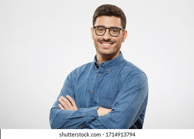 Young business man wearing blue shirt and glasses, looking at camera with positive confident smile, holding arms crossed, isolated on gray background