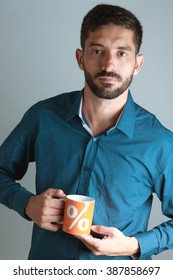 Young business man wearing blue shirt, drinking coffee / tea in orange mug with percent sign