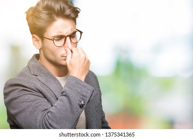 Young business man wearing glasses over isolated background smelling something stinky and disgusting, intolerable smell, holding breath with fingers on nose. Bad smells concept.