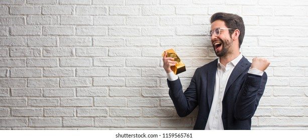 Young business man wearing a suit against a white bricks wall very happy and excited, raising arms, celebrating a victory or success, winning the lottery