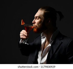 Young business man in white shirt and jacket drinking red martini cocktail drink  looking at the corner on dark background