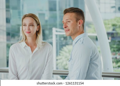 Young business man and woman discuss business or talking about work outside office. Businesspeople talking together in front of office building. Work romance.