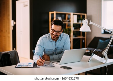 Young business man working at home with laptop and papers on desk