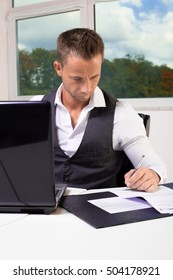 young business man working at a laptop and sign a document