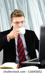 Young business man working in the office and drinking coffee