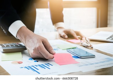 Young Business man working at office with laptop,smartphone mobile,post it note,calculator and graph data documents   for  Plans to improve quality next month on his desk.
