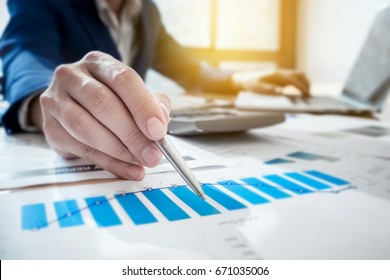Young business man working at office with laptop computer ,calculator and graph data documents   for  Plans to improve quality next month on his desk.