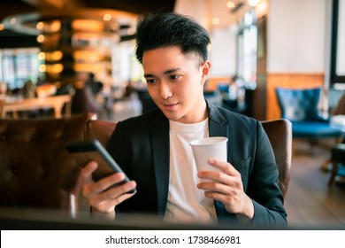 young Business man  Working On Laptop and mobile phone In Coffee Shop
