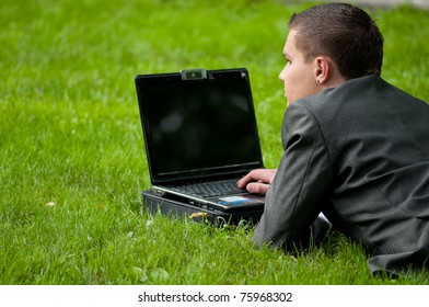 Young business man working on notebook laptop computer, at green park. Student.
