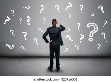 Un jeune homme d'affaires écrit un point d'interrogation sur le tableau