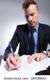 young business man writing something on a form. on a light gray studio background