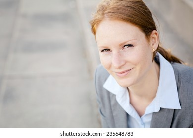 Young business manager or assistant smiles at the camera.