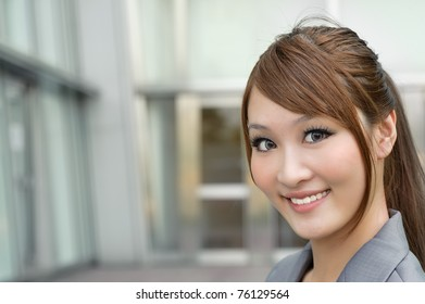 Young business manager woman smiling and looking at you, closeup portrait outside of modern buildings with copyspace.