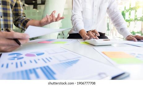 junge Geschäftsleute, die mit neuen Startprojekten arbeiten, die mit einem Plan auf dem Schreibtisch und einem modernen digitalen Computer arbeiten.