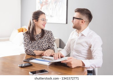 Young business married couple sitting at table and reading a book