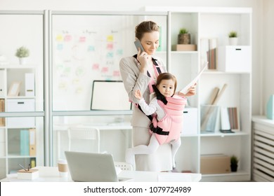 Young business mom with her cute baby in carrier talking by smartphone and consulting her clients
