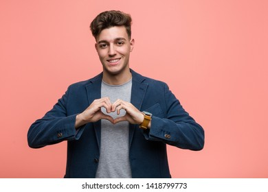 Young business natural man smiling and showing a heart shape with him hands.