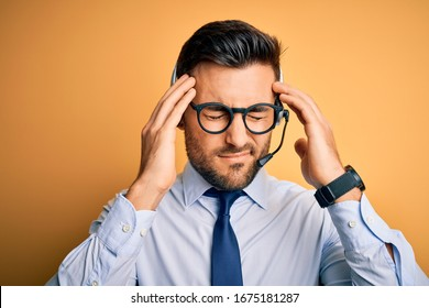 Young business operator man wearing customer service headset from call center suffering from headache desperate and stressed because pain and migraine. Hands on head.