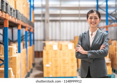 Young business owner portrait. Young chinese woman in suit pose smile with bottle warehouse in background.