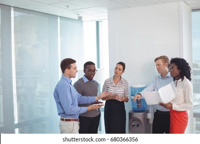Young business partners discussing while standing at office