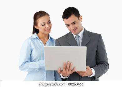 Young business partners looking at laptop against a white background