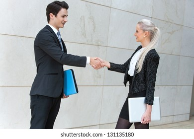 Young business partners shaking hands over deal outdoors.