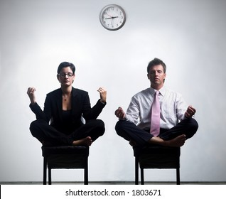 Young business people in an abstract office environment are sitting in yoga lotus-pose and relaxing.
