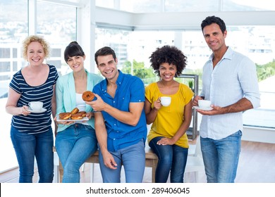 Young business people eating donuts and drinking