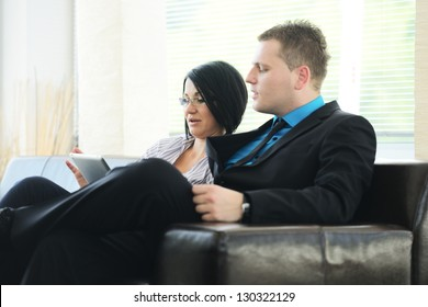 Young business people having meeting at office sitting on sofa talking