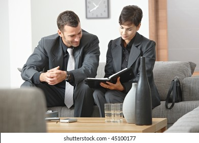 Young business people having meeting at office sitting on sofa working in team.