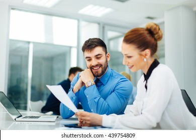 Young business people look at paper documents. Selective focus on man face.