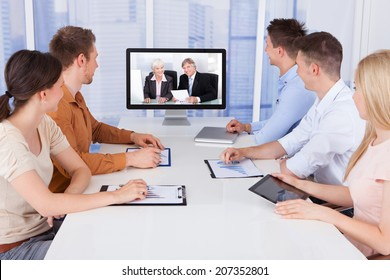 Young business people looking at computer monitors in conference room