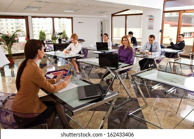 young business people meeting with their leader. modern office classroom with students listening to their trainer