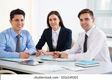 Young business people in office smiling looking at camera
