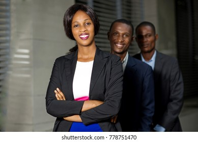 Young business people in a row, smiling for a business meeting.