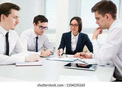 Young business people are sitting around the table at a meeting in the office
