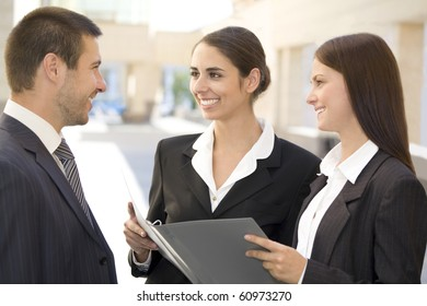 Young business people talk against a building of modern office
