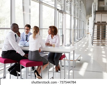 Young business people talking in modern lobby, full length