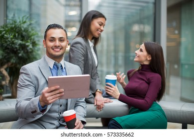 Young business people talking in office and drinking coffee