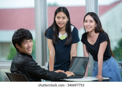 Young business people team sitting at desk, using computer at business training, smiling
