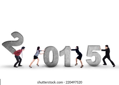 Young business people try to compose number 2015 in studio, isolated over white background