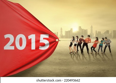 Young business people try to pull number 2015, symbolizing an effort for progress in 2015