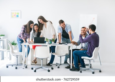 Young business people work in a team. Planning a project strategy, sharing ideas, preparing presentations, coaching concept. Women and men sit at a table with notebooks and a laptop in a light room