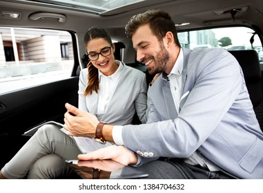 Young business people working together while traveling by a car. They are using laptop and preparing for meeting.