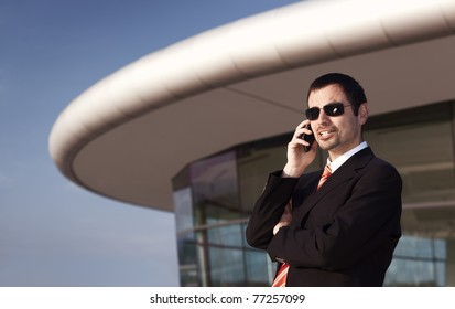 Young business person in black suit and sunglasses talking on mobile phone with office building and blue sky in background.