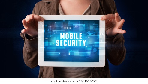 Young business person working on tablet and shows the digital sign: MOBILE SECURITY