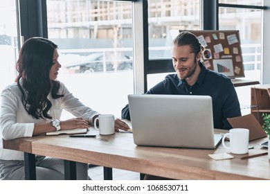 Young business professionals. Group of young modern people in smart casual wear discussing business while sitting in the creative office - Shutterstock ID 1068530711