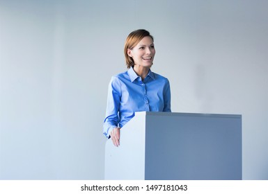 Young business speaker smiling while standing in conference room
