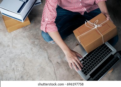 Young business start up online seller owner using computer for checking the customer orders from email or website and preparing packages for product office equipment.